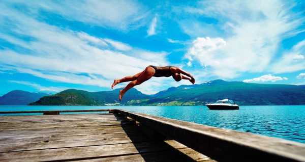 Open water swimmer diving into blue ocean with boat in background