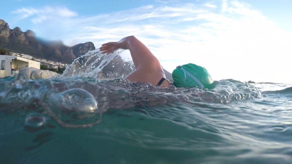 Female swimmer with green cap swimming freestyle in ocean