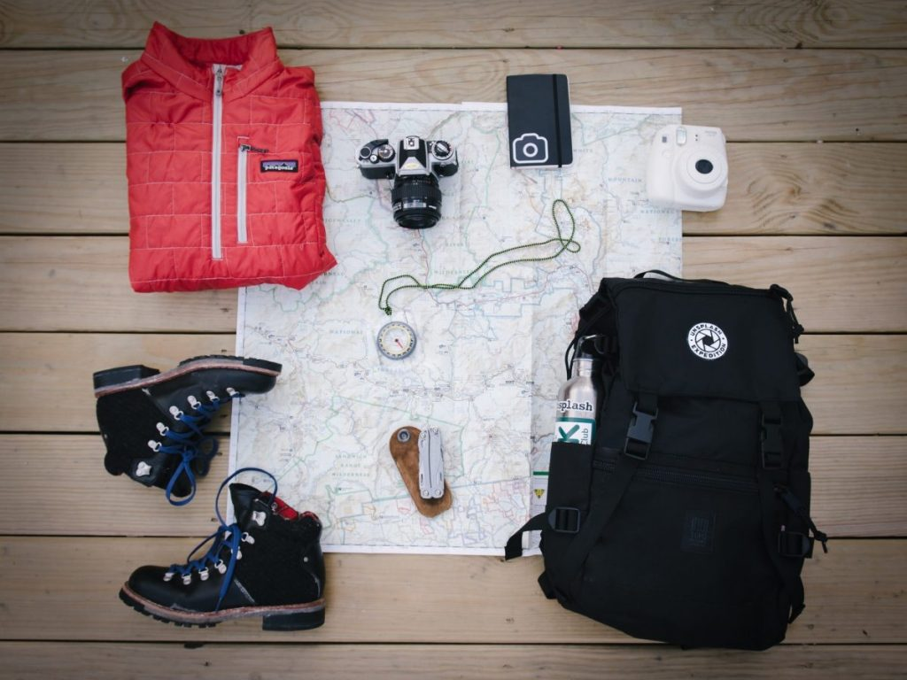 Trail running gear spread out including backpack shoes and jacket