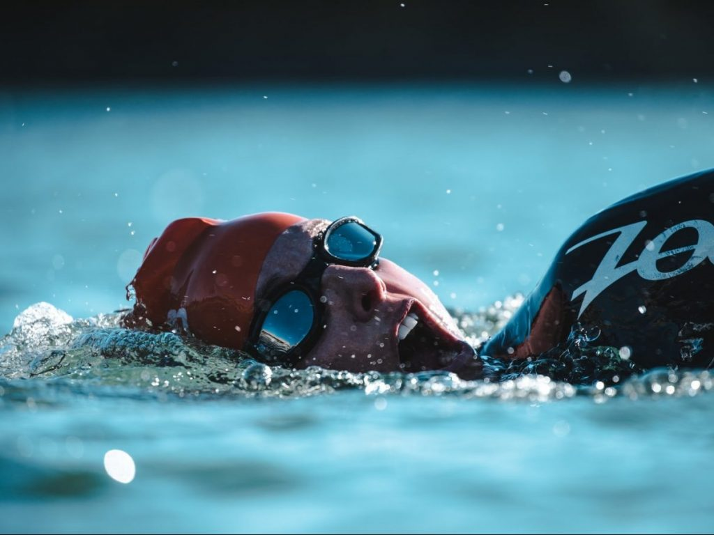 open water swimmer red cap breathing to side